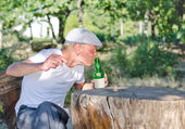 Man taking a swig of alcohol from a bottle — Stock Photo