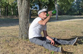 Alcoholic sitting drinking in a park — Stock Photo