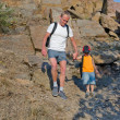 Man helping his son to hike on a rough area — Stock Photo