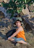 Young boy waiting alongside his rucksack — Stock Photo