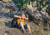 Carino piccolo ragazzo seduto su un pendio di montagna — Foto Stock