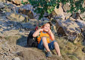 Cute little boy sitting on a mountain slope — Stock fotografie