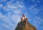 Man sitting on top of a rocky pinnacle — Stock Photo