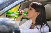 Alcoholic woman drinking a driving — Stock Photo