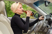 Young female driver drinking and driving — Stock Photo