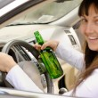 Stock Photo: Female driver drinking and driving