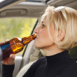 Stock Photo: Young female driver drinking bear in car