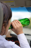Woman driver drinking while driving on a road — Stock Photo