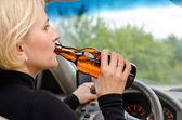 Woman alcoholic drinking as she drives the car — Stock Photo