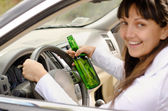 Female driver drinking and driving — Stock Photo