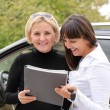 Two women signing a contract to buy a car — Stock Photo