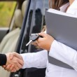 Saleslady selling a car and shaking hands — Stock Photo