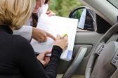 Two woman signing a deal to purchase a car — ストック写真
