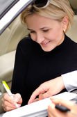 Woman signing a deal to purchase a car — Stok fotoğraf