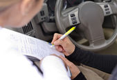 Woman drivier signing a legal document — Stock Photo