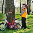 Little boy standing grinning alongside his bicycle — Stock Photo #33054343