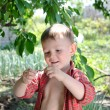 Smiling little boy holding a wriggling worm — Stock Photo