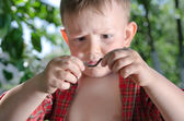 Curious little boy with a worm — Stock Photo