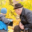 Boy using a tablet pc with grandfather watching — Stock Photo