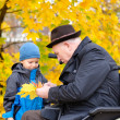 Elderly disabled man playing with his grandson outdoors — Stock Photo