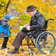 Elderly disabled man with his grandson — Stock Photo