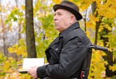 Pensive man reading on park in autumn — 图库照片
