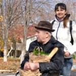 Woman taking an elderly disabled man shopping — Stock Photo