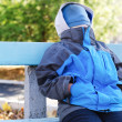 Young boy sitting on a bench with his face covered — Stock Photo