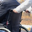 Woman pushing a disabled man in a wheelchair — Stock Photo #34436687