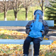 Young boy sitting on a bench into park with his face covered — Stock Photo