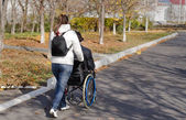 Carer taking a disabled man for a walk — Stock Photo