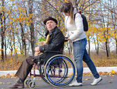 Woman pushing an elderly man in a wheelchair — Stock Photo
