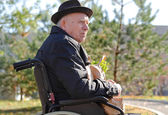 Elderly man in a wheelchair enjoying the sun — Stock Photo