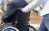 Woman pushing a disabled man in a wheelchair — Stock Photo