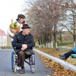 Disabled man and his carer chat to a little boy — Stock Photo