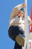 Cute active child climbing up a ladder in the park — Stock Photo