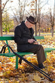 Handicapped elderly man sitting in the park — Stock Photo
