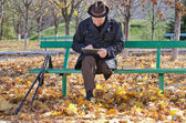Elderly man on crutches using a tablet in the park — Stock Photo