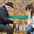 Elderly man arguing during a game of chess with woman sit together on a wooden park bench — Stock Photo