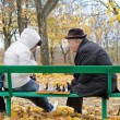 Three generations of a family playing chess in park beanch — Stock Photo