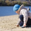 Cute little boy playing on a sandy beach — Stock Photo