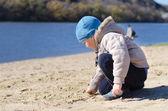 Cute little boy playing on a sandy beach — Stock Photo