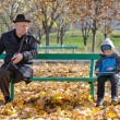 Стоковое фото: Elderly handicapped mwatching young boy
