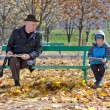 Стоковое фото: Grandfather watching over his young grandson