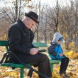 Retired man reading in the park with his grandson — Stock Photo