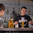 Barman serving customers at the bar counter — Stock Photo