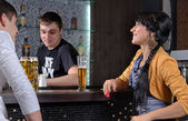 Barman socialising with customers at the bar — Stock Photo
