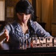 Female alcoholic downing a row of shots — Stock Photo