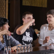 Group of friends downing shots of vodka — Stock Photo