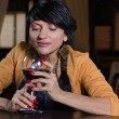 Woman holding a glass of red wine at the bar — Stock Photo